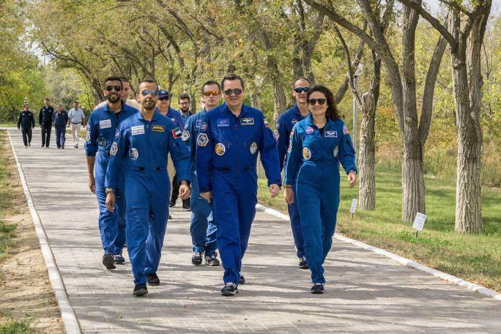 jsc2019e053724 - At the Cosmonaut Hotel crew quarters in Baikonur, Kazakhstan, spaceflight participant Hazzaa Ali Almansoori of the United Arab Emirates (left), Oleg Skripochka of Roscosmos (center) and Jessica Meir of NASA (right) lead the way down the W